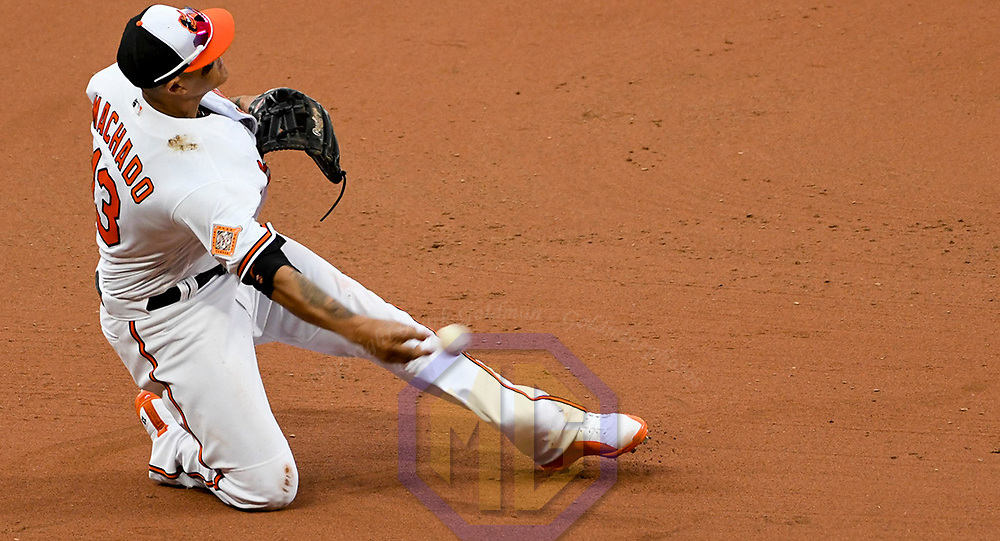 BALTIMORE, MD - APRIL 03: Baltimore Orioles third baseman Manny Machado (13) makes a diving catch and throws to first base in the eleventh inning against the Toronto Blue Jays on April 3, 2017, on Opening Day at Orioles Park at Camden Yards in Baltimore, MD.   The Baltimore Orioles defeated the Toronto Blue Jays, 3-2 in eleven innings.  (Photo by Mark Goldman/Icon Sportswire)
