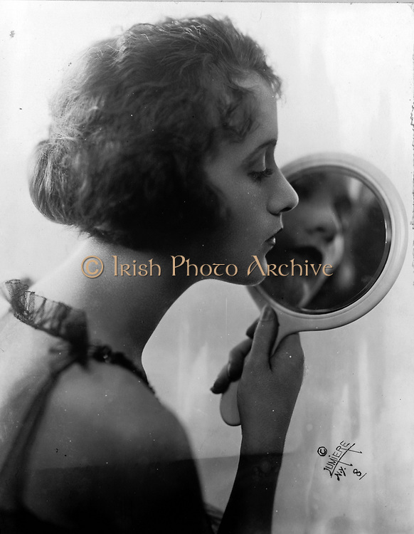 Constance Talmadge, American Silent Movie actress, looking into mirror 1921