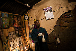 A midwife helps a woman give birth in his home in Mathare, a poor slum in Nairobi, Kenya.  Most women in Mathare can not afford to go to a hospital to give birth; they can not even afford the 10 minute taxi ride to get there.  The expecting mothers have no prenatal care and arrive to the midwives' homes once labor has already begun.  The midwives have no supplies and are usually have no formal training.  The mothers often give birth on dirt floors with no medicine, and their babies' umbilical cords are cut with dirty scissors and they are washed with tap water.