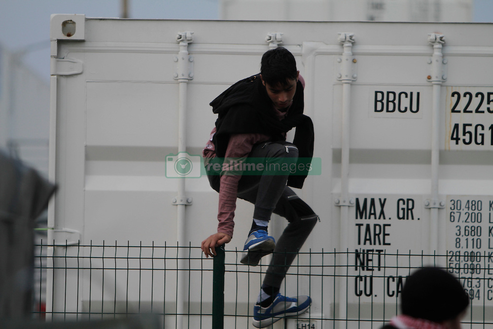 October 24, 2016 - Calais, Nord-Pas-de-Calais-Picardie, France - A refugee climbs over the fence, to leave the official camp. The French state has started processing the inhabitants of the Jungle refugee camp in Calais and distribute them to centres around France. Not all of the 6 to 10 thousand refugees living in the Jungle (according to different estimates) are expected to leave voluntarily and some have already disappeared. (Credit Image: © Michael Debets/Pacific Press via ZUMA Wire)
