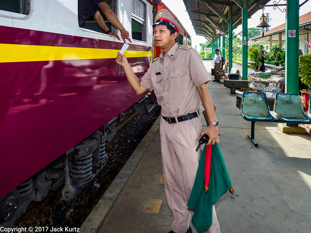 31 MAY 2017 - CHACHOENGSAO, THAILAND: A station master picks up paperwork from a conductor on a Bangkok-Chachoengsao commuter train at the train station in Chachoengsao, a provincial town about 50 miles and about an hour by train from Bangkok. The train from Chachoengsao to Bangkok takes a little over an hour but traffic on the roads is so bad that the same drive can take two to three hours. Thousands of Thais live outside of Bangkok and commute into the city for work on trains, busses and boats.       PHOTO BY JACK KURTZ