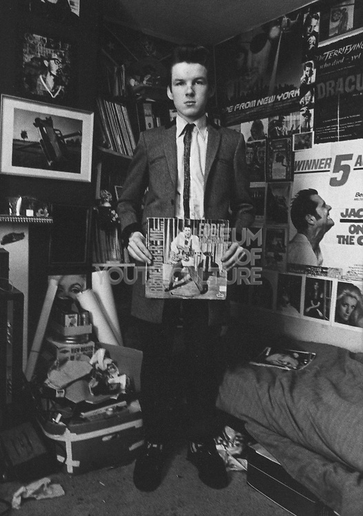Rock'n'roll fan in his bedroom holding a Eddie Cochran record