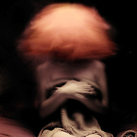 Dark conceptual portrait of a young women with orange moving hair.