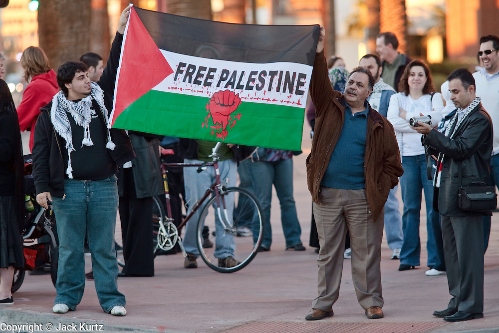 30 DECEMBER 2008 -- PHOENIX, AZ: Palestinian men hold up the Palestinian flag during a pro-Palestinian - anti-Israeli demonstration in Phoenix, AZ, Tuesday. About 200 people from a variety of human rights and peace activists organizations in Phoenix, AZ, marched in opposition to the Israeli attacks on Gaza and in favor of Palestinian rights on Tuesday, the fourth day of Israeli air strikes on Hamas facilities in Gaza. Photo by Jack Kurtz / ZUMA Press