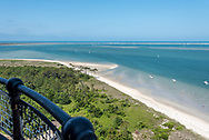 View from the top of Cape Lookout Lighthouse with beautiful blue water, white sand beach, greenery, and black railing of lighthouse.