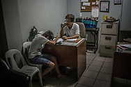 Orly Fernandez, operations manager at Eusebio Funeral Home talks to Ginnalyn Soriano, 21, as she breaks down while filling out paper work, moments after her 24 year old elder brother, Julius was shot to death during a police drug operation in Caloocan, Metro Manila.  Malabon, Metro Manila, Philippines