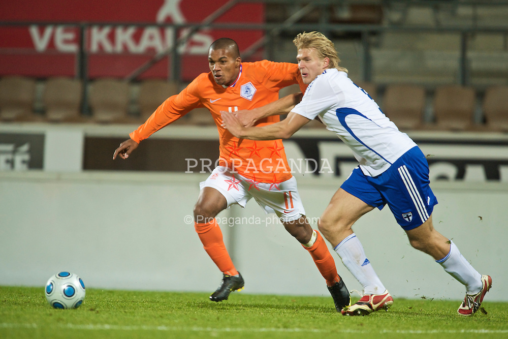 HELSINKI, FINLAND - Friday, October 9, 2009: The Netherlands' Diego Biseswar (Feyenoord) and Finland's Paulus Arajuuri (IFK Mariehamn) during the UEFA Under-21 Championship Qualifying Round Group 4 match at the Finnair Stadium. (Pic by David Rawcliffe/Propaganda)