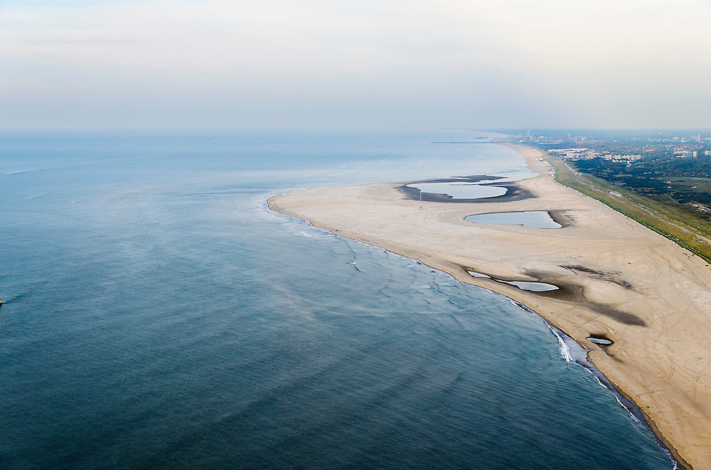 Nederland, Zuid-Holland, Gemeente Westland,  28-09-2014; Delflandse Kust ter hoogte van Ter Heijde en Monster, Den Haag aan de horizon. De Zandmotor is een kunstmatig schiereiland ontstaan door het opspuiten van zand voor de kust. Wind, golven en stroming zullen het zand langs de kust verspreiden waardoor breder stranden en duinen ontstaan. De zandmotor is een experiment in het kader van kustonderhoud en kustverdediging. <br />