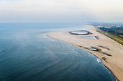 Nederland, Zuid-Holland, Gemeente Westland,  28-09-2014; Delflandse Kust ter hoogte van Ter Heijde en Monster, Den Haag aan de horizon. De Zandmotor is een kunstmatig schiereiland ontstaan door het opspuiten van zand voor de kust. Wind, golven en stroming zullen het zand langs de kust verspreiden waardoor breder stranden en duinen ontstaan. De zandmotor is een experiment in het kader van kustonderhoud en kustverdediging. <br /> Sand Engine, artificial peninsula build by the raising of sand for the coast of Ter Heijde (near the Hague, at the horizon). Wind, waves and currents will distribute the sand along the coast yielding wider beaches and dunes along the coastline. The Sand Engine is a experiment for coastal maintenance of coastal defense.<br /> luchtfoto (toeslag op standard tarieven);<br /> aerial photo (additional fee required);<br /> copyright foto/photo Siebe Swart