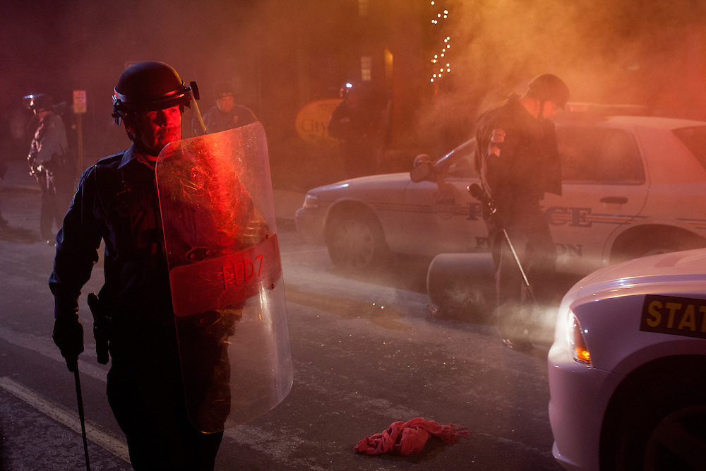 A policeman stands guard as a squad car, set on fire by protestors, burns out in front of Ferguson City Hall. Law enforcement officers used tear gas to disperse a group of violent demonstrators who set dozens of fires across the Ferguson area.