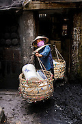 Female porter carries a yoke filled with ceramic pots at either end as she emerges from the doorway of the factory in Battrang, North Vietnam.