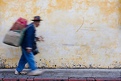 Mayan man carrying load on his back walking in front of colorful, painted wall, Antigua, Guatemala