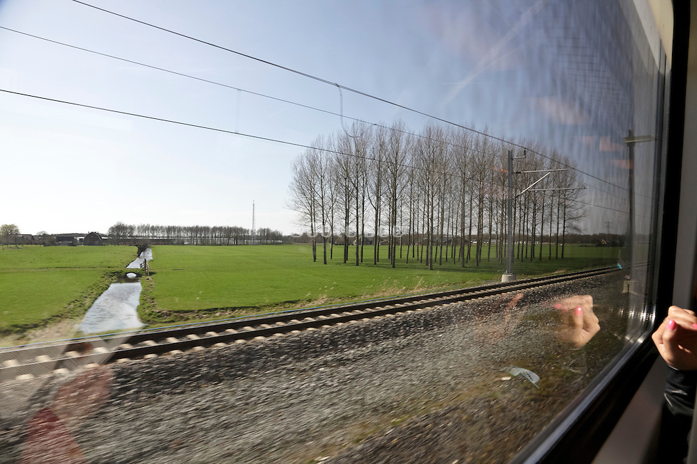 Dutch landscape near Utrecht seen from train window reflecting female hand with pink nails