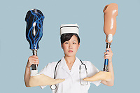 Female doctor holding up two artificial legs over light blue background