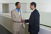 Two business men shaking hands in office hallway