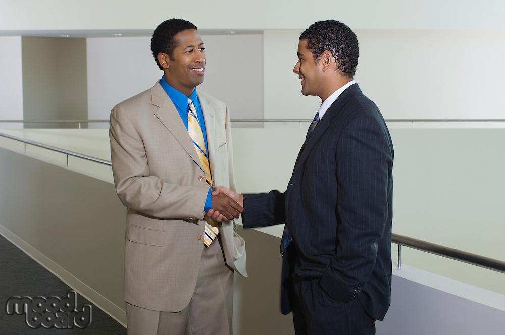 Two business men shaking hands in office hallway