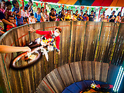 24 NOVEMBER 2018 - BANGKOK, THAILAND:  A Thai daredevil rides a motorcyle in the motordrome at the Red Cross Fair. The motordrome is a traditional Thai entertainment event at rural fairs. A daredevil rides a motorcycle on the vertical walls of an enclosed circular track. Spectators hold out money and the daredevil plucks it out of their hands as he goes past them. The Red Cross Fair is a fund raiser and annual event in Bangkok that draws thousands of attendees every night of its nine day run. The fair features games of chance, a midway with rides, handicrafts and food. This is the first year the fair has been in Lumpini Park. Previously it had been held in the Dusit section of Bangkok. The 2018 Fair marks 125 years of service for the Red Cross in Thailand.     PHOTO BY JACK KURTZ