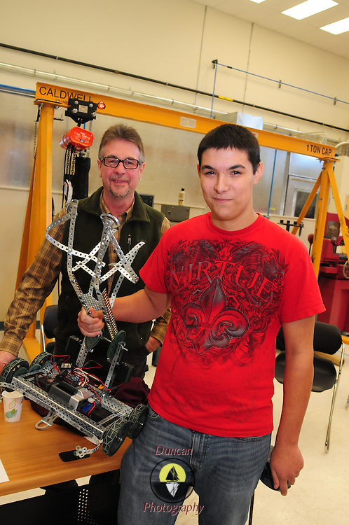 BRUNSWICK, Maine --  12/17/13 --   Winning driver, Casey Roy and his teacher, Mark Richards, of Lewiston Regional Technical Center pose during the robotics competition at Southern Maine Community College (SMCC) last Tuesday. High School Students from Portland, Lewiston and Kennebunk gathered at SMCC's Brunswick center for their first robotics competition. A Bank of America grant to Portland and Lewiston started them up last spring -- giving an opportunity for young adults to work in teams to conceive, build, program and operate the small robots.  Photo © Roger S. Duncan 2013.