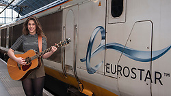 © Licensed to London News Pictures. 08/04/2015. St Pancras International Station, London, UK.  Natalie Shay, a 16 year old musician from Enfield, North London, and a current student at the BRIT School for performing arts boarding the Eurostar train to perform in Paris.  Her trip comes as a result of being awarded the Eurostar prize as well the Youth Category in last year's Gigs busking competition, organised by City Hall.  The talented singer-songwriter has already picked up several music awards, in addition to her Gigs accolades, including the Undiscovered Talent category at the 2014 London Music Awards, as well as playing at major venues around London, including the Roundhouse and the 100 Club. Photo credit : Stephen Chung/LNP