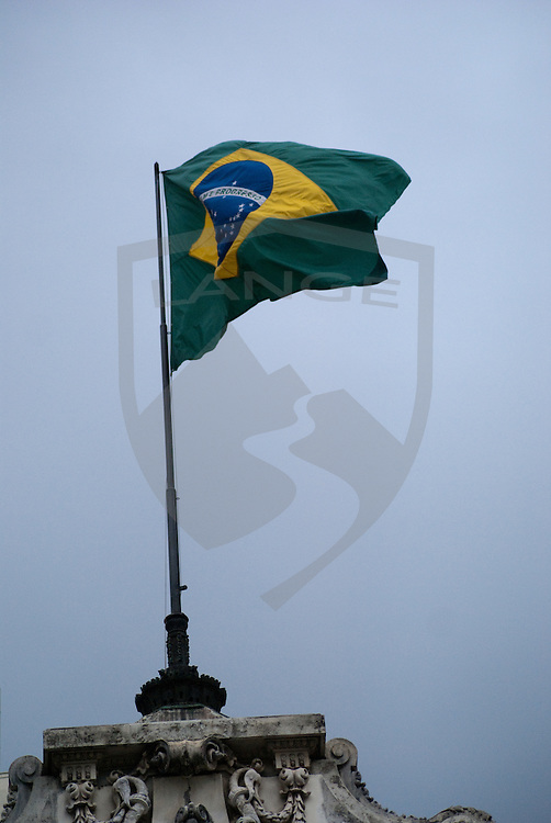 the brazilian flag blows in the wind framed by an overcast sky in rio de janeiro, brazil