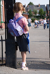 Little girl at school gate looking into the playground,