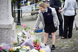 © Licensed to London News Pictures. 17/06/2016. Birstall UK. A child lays a single rose at the scene in Birstall market place this morning where MP Jo Cox was murdered yesterday. Photo credit: Andrew McCaren/LNP