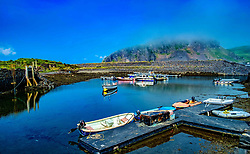 The tiny harbour on Easdale Island with Seil Island shrouded in low cloud in the background.  Easdale Island, the smallest permanently-inhabited island of the Inner Hebrides, Scotland<br /> <br /> (c) Andrew Wilson | Edinburgh Elite media
