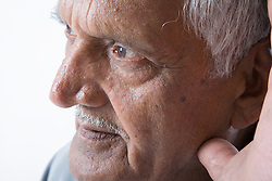 Portrait of an older man cupping his ear to hear better,