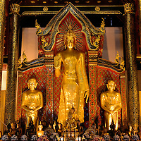 """Presiding Buddha at Wat Chedi Luang in Chiang Mai, Thailand <br /> This ornate Theravādin shrine at Wat Chedi Luang features the 14th century Presiding Buddha which is called Phra Chao Attarot.  This standing mudrā with his right palm extended is the """"Preventing Relatives from Fighting"""" position.  The Lord Buddha was trying to silence relatives from a disagreement over limited water supplies.  This posture also symbolizes """"Peace to the World."""""""