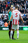referee Stuart Attwell shows Stoke City defender Kevin Wimmer (#5) a yellow card for a late sliding tackle during the Premier League match between Newcastle United and Stoke City at St. James's Park, Newcastle, England on 16 September 2017. Photo by Craig Doyle.
