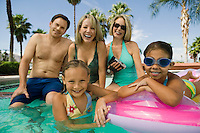 Two girls (7-9) with parents and grandmother in swimming pool portrait.