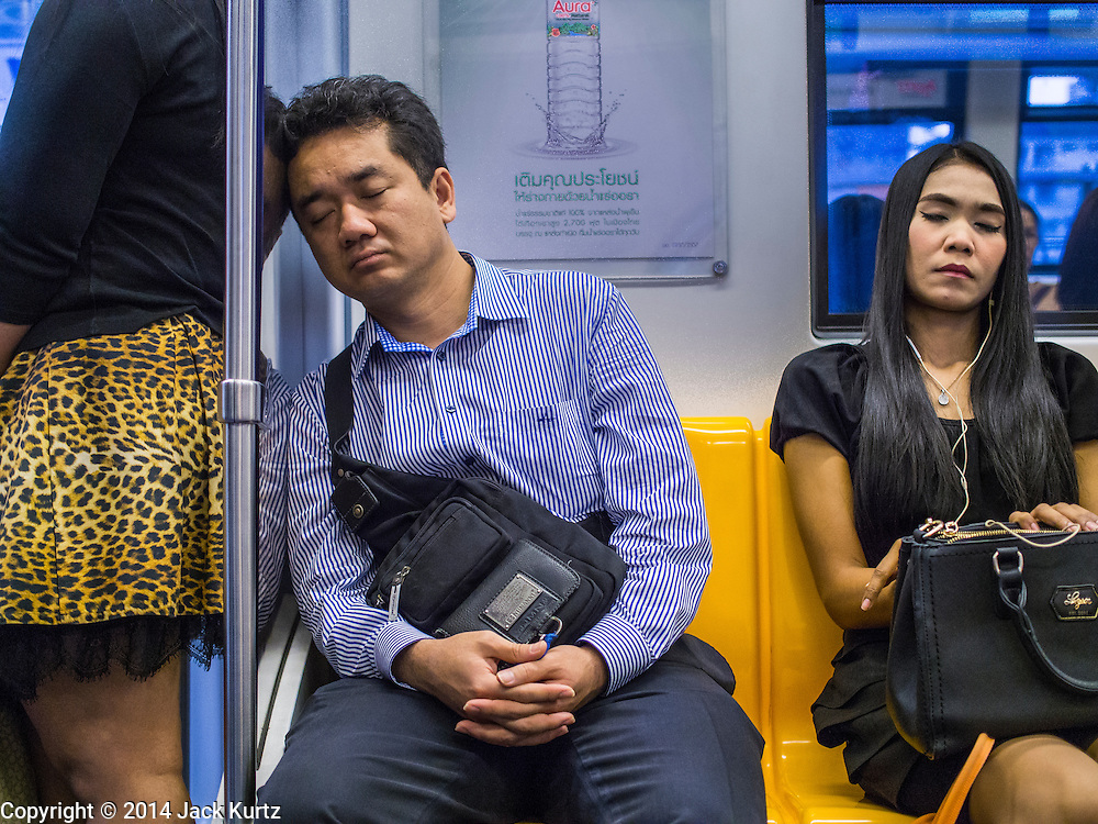 28 OCTOBER 2014 - BANGKOK, THAILAND: Passengers sleep on the Silom line of the Bangkok Skytrain. While there are two train tracks for most stretches of the Skytrain system, the portion of the Silom line on the Saphan Taksin Bridge spanning the Chao Phraya River has just one track due to limited space, causing a bottleneck when an outbound train and inbound train arrive at the bridge at the same time. The Bangkok Metropolitan Authority (BMA) had sought permission from the Department of Rural Roads to expand the Taksin Bridge in order to make way for an additional track, but the department had said it was not possible. The Saphan Taksin  station was originally supposed to be temporary and is one of the busiest on the system. It's a connecting station for the Chao Phraya River boats used by Thai commuters coming into the city from neighboring provinces and tourists who use the boats to go upriver into the old parts of Bangkok from the central business district. More than 4,000 commuters a day use the station. The BMA plans to build an elevated moving sidewalk to the river from Surasak BTS station about one kilometer away. Surasak is the nearest station to Saphan Taksin. The Skytrain system has a combined length of 36 kilometres and includes 34 stations, including Saphan Taksin.        PHOTO BY JACK KURTZ