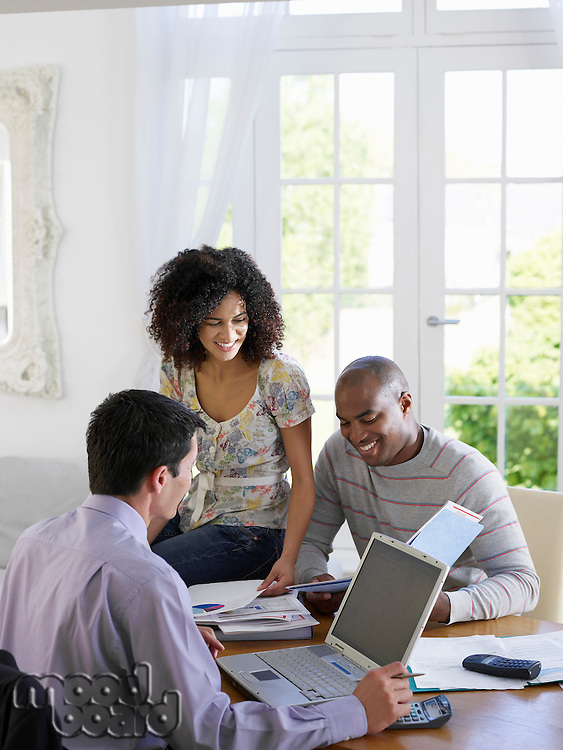 Young African American couple discussing home finances with financial advisor at dining room table