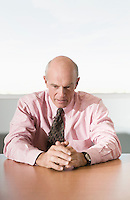 Serious Businessman Sitting at Meeting Table