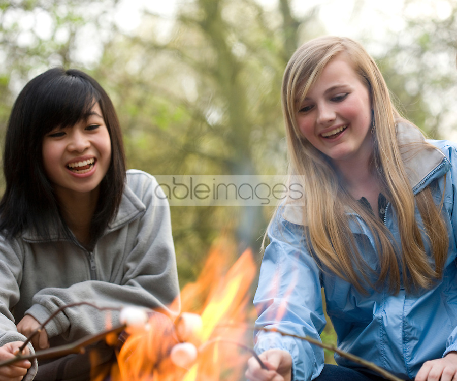 Two smiling teenaged girls roasting marshmallow over a campfire