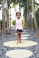 Girl (5-6 years) standing on stepping stone on path portrait
