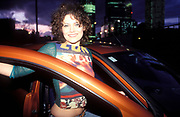A women at a car with open door, smiling, Canary Wharf, London, 2004
