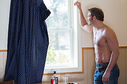 shirtless man looking out a window in a cheap and dirty motel room