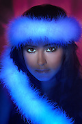 Portrait of a young woman with a glowing feather boa.Black light