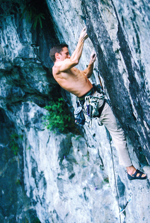 A fit adult male rock climber ascending cliff face with harness and rope.