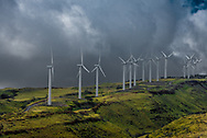 A row of windmills sits high on top of a mountain in Maui, Hawaii