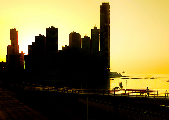 Yellow sun rises behind the high rise condominiums of Punta Paitilla, a residential neighborhood located on the Pacific Ocean in Panama City, Panama.  A pedestrian bridge allows people to walk over  busy Balboa Avenue and into the Cinta Costera, a beltway of parks and green spaces.