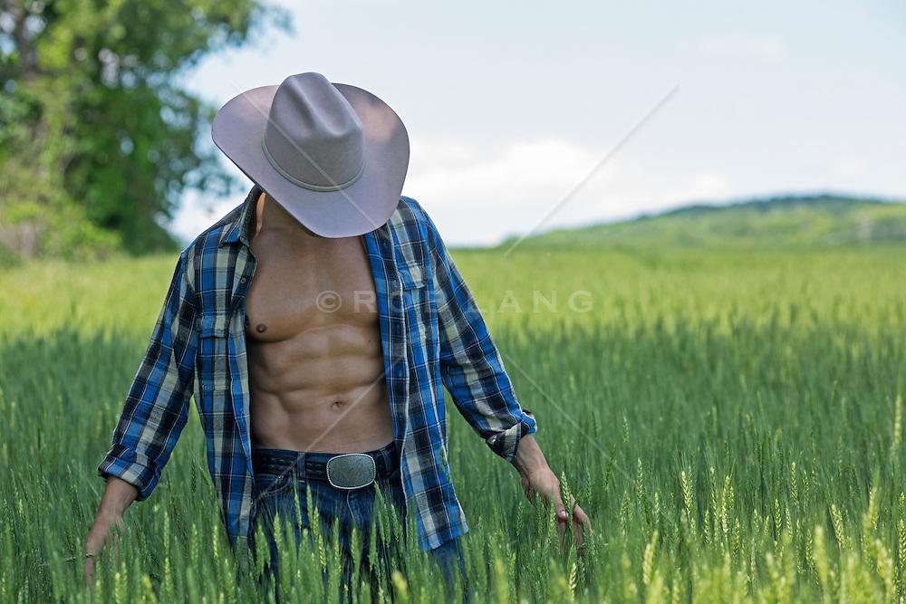 muscular cowboy with an open shirt standing in a green field of grass