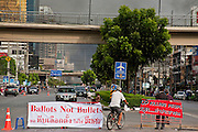 May 19 - BANGKOK, THAILAND: A man pedals his bike past an anti government road block on Rama IV Road while smoke from the front line of the Rama IV barricades and battle billows into the sky. The Royal Thai Army attacked anti-government protesters May 19 with troops and armored personnel carriers. Photo by Jack Kurtz