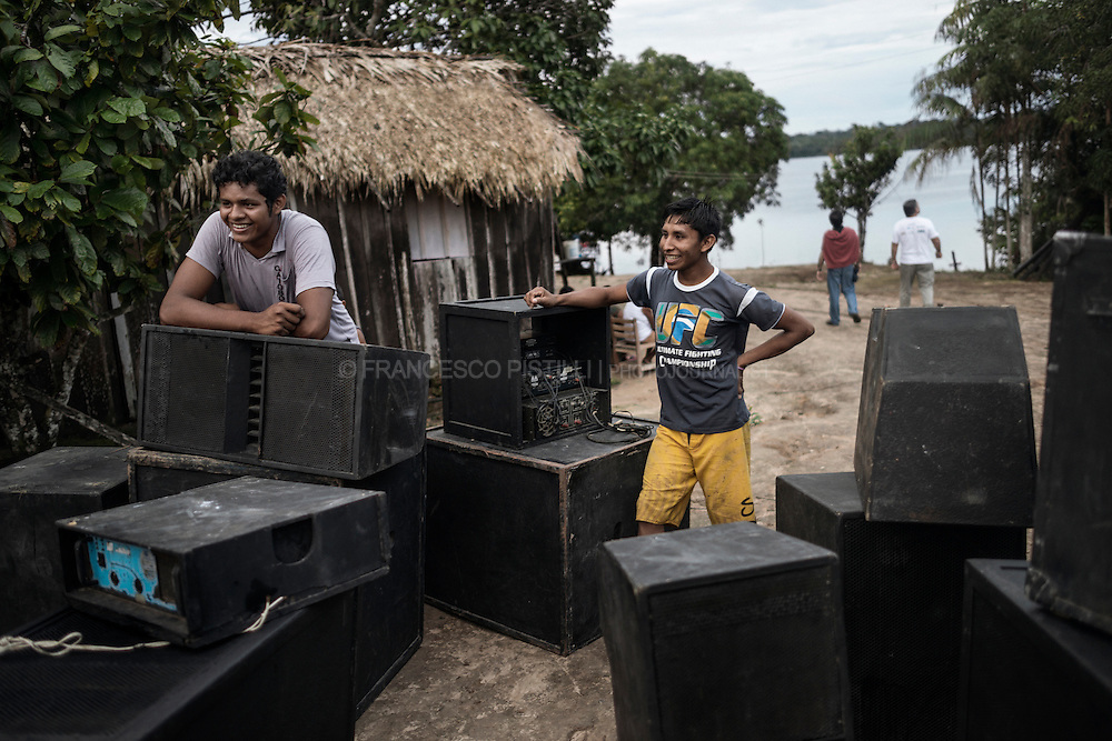 "Guaranatuba village, located alongside of the Andira riverbank. Two young Satere Mawe are preparing a powerfull sound system for the ""guarana harvest fest"" that hosts music, traditional dance, speeches about indigenous culture and politics."