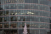 An artificial Christmas tree and the many storeys of corporate offices, on 6th December 2017, in London England.