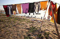 cloths drying in the foreground with women cleaning on the ganges river, india