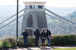 © Licensed to London News Pictures; 22/03/2020; Bristol, UK. Coronavirus Pandemic; people look at the Clifton Suspension Bridge on a sunny weekend, after the UK's prime minister ordered the closure of all pubs, bars, cafes, restaurants and indoor gyms to try and prevent the spread of the coronavirus. The UK Government is urging people to maintain social distance but also to get fresh air and exercise outside with social distance between people. Photo credit: Simon Chapman/LNP.