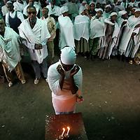 Ethiopian men and women pray as they light candles for the Friday prayer at the synagogue  in Gondar, Ethiopia, May 2008.