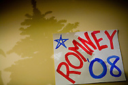 A Christmas tree casts a shadow over a sign on the wall during a campaign stop by former Massachusetts governor Mitt Romney in Manchester, N.H., on Friday, Jan. 4, 2008.